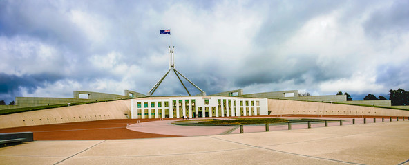 Panoramic view of Australian Parliament House with storm clouds above. Canberra, Australian Capital Territory, Australia.