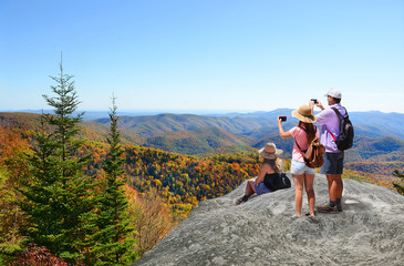 People hiking in autumn mountains enjoying beautiful mountain view. Father  with his family on top of mountain, taking photos of beautiful mountains with iphones. North Carolina, USA.