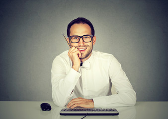 Smiling young handsome man sitting in front of computer keyboard