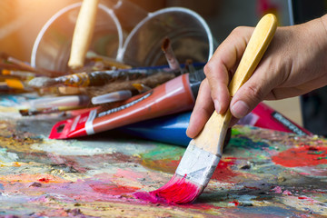 artist paints a picture of oil paint brush in hand with palette closeup