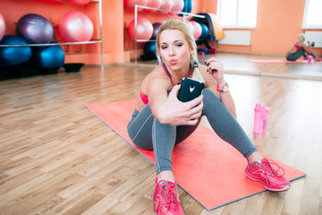 Athlete woman taking selfie at gym. Fitness glamour blonde making duck face and self photo for Instagram while training .