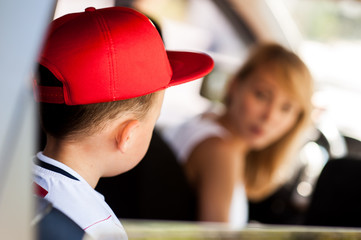 Mother and son sitting in the car and discuss the upcoming visit on holiday