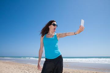 woman making selfie teasing at beach