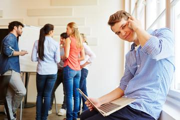 Junger Student mit Handy und Laptop