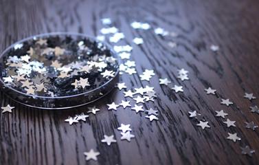 Новогодний декор, серебряные звездочки конфетти, глиттер на деревянном фоне.