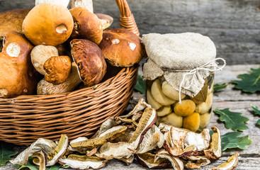 Porcini mushrooms pickled in jar and dried mushroom on rustic ba