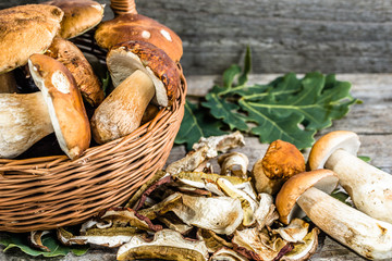 Dry mushrooms and harvested boletus mushroom in a basket on rust
