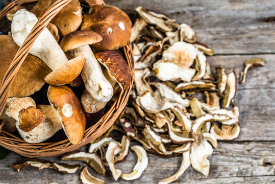 Fresh boletus mushrooms in a basket and dry mushrooms on wooden