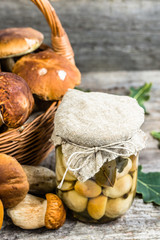 Boletus mushrooms pickled in jar on rustic wooden table, autumna
