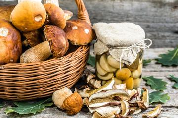 Boletus mushrooms pickled in jar and dried mushroom on rustic ba