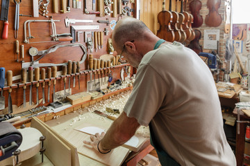 Violin maker cutting wood to be used for new instrument
