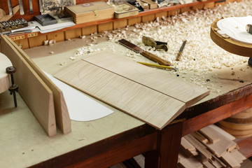 Wood on workbench of instrument maker waiting to become a violin