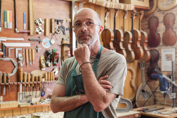 Instrument maker in his workshop looking into camera