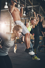 Men and women doing pull ups on bar in gym