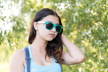 Portrait of teen girl in sunglasses on nature summer