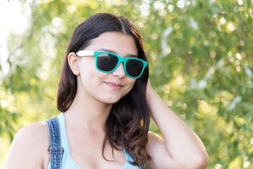 Portrait of teen girl in sunglasses on nature summer