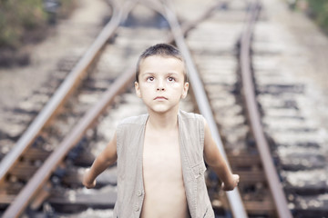 boy with arms outstretched standing on the railway line