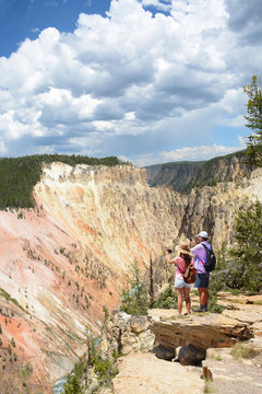 Family on hiking trip. Father and daughter taking photos of beautiful mountains with iphones. Yellowstone National Park, USA.
