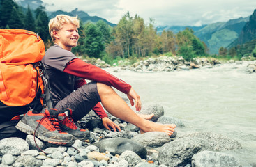 Young tourist man rest on the mountain river bank