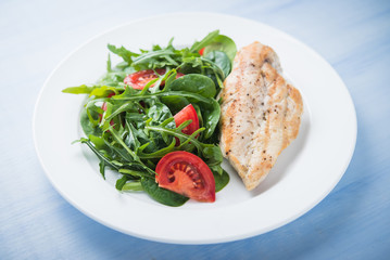 Roasted chicken breast and fresh salad with tomato and greens (spinach, arugula) close up on blue wooden background. Healthy food.