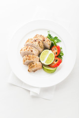Sliced lime pork tenderloin on white wooden background top view. Healthy food.