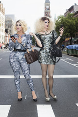 Two drag queens using mobile phones while standing on street