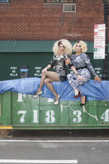 Two drag queens sitting on a skip