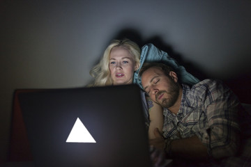Young couple looking at a laptop in bed