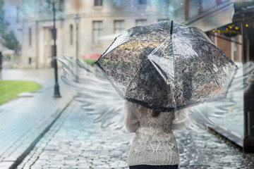 Woman with angel wings is the city under an umbrella