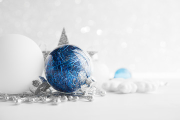 Blue and white xmas ornaments on glitter holiday background. Merry christmas card. Winter theme. Happy New Year.
