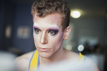 Young man applying drag makeup