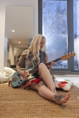 Young woman playing electric guitar while sitting at home