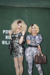Two drag queens standing outdoors