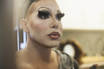 Performer checks dramatic makeup in mirror