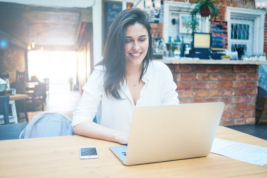 Modern businesswoman with long brown hair is smiling at the screen of a laptop in a coffee shop. A caucasian brunette female student is sitting at the table with a portable computer and a smartphone.