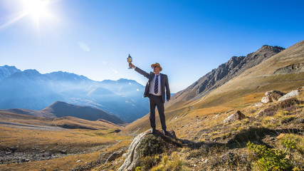 a man in a suit with a sports cup, mountain panorama, summer