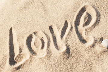 Love, word - written by hand in sand on a sea beach