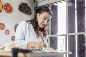 artisan whittling wood in wood carving atelier