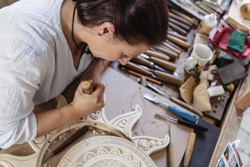 Woman working on wooden flourish carving with whittle