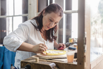 Woman in whittlers atelier finishing her piece of work with paint