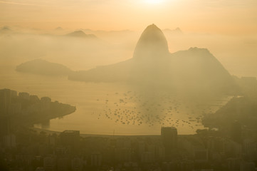 Misty golden sunrise skyline of Rio de Janeiro, Brazil with silhouette of Sugarloaf Mountain and Guanabara Bay