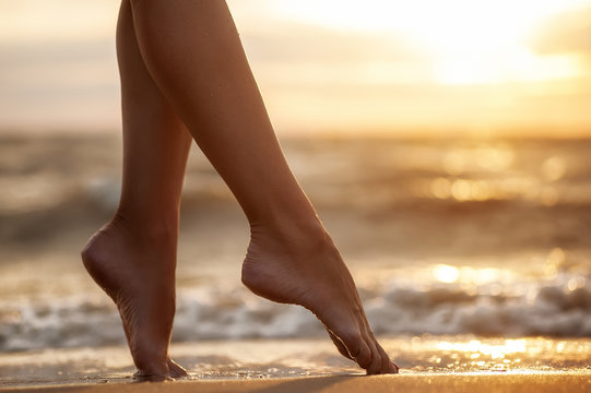 sexy woman's legs  on the sandy  beach with the sea water and su