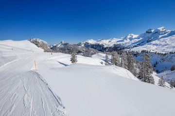 View to Skiers on the ski slopes and Swiss Alps covered by fresh new snow seen from Hoch-Ybrig ski resort, Central Switzerland