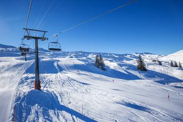Skiers on the slope from the Spirstock peak in Hoch-Ybrig ski resort, Swiss Alps, Schwyz, Central Switzerland