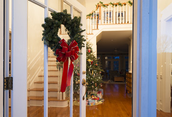 Glass door with wreath open to foyer with Christmas tree