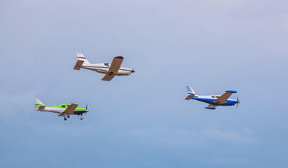 Three small aircraft flying in the sky against a background of clouds next to each other.