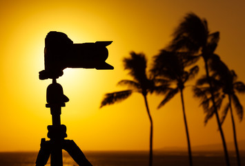 DSLR camera on a stand against a beautiful sunset. Outdoor photography concept.