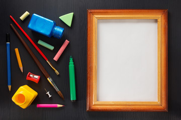 paint supplies and frame on black wood