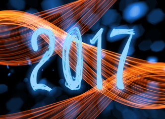 Happy new year 2017 isolated numbers written with sparkle light on black blurred bokeh background frame