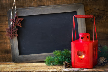 Red Christmas lantern with fir pranches, pine cones and an empty blackboard against dark rustic wooden background. With plenty of copy space for your text and festive wishes